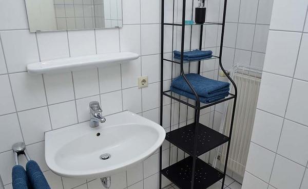 Bad mit Badewanne und Duschvorhang, WC, Spültisch und Spiegel