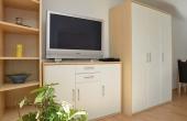 Wohnbereich mit TV, Regal und Schränken