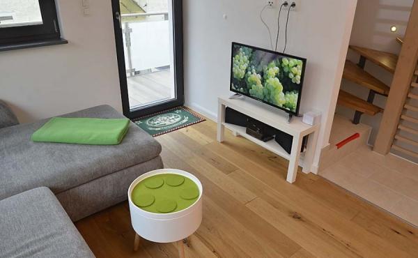 Großzügiger Wohnbereich mit TV, Stereoanlage und WLAN, Zugang zum großen Balkon - Ferienhaus Weinhäusel, Weindorf Hambach, Neustadt / Weinstr. (Pfalz)