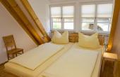 Schlafzimmer mit Doppelbett und Kleiderschrank, alles aus Massivholz - Ferienwohnung Idig, Weingut Thomas Steigelmann, Gimmeldingen (Pfalz), Neustadt / Weinstr.