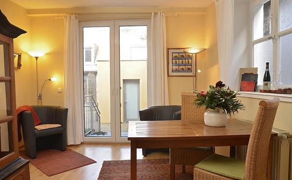 Wohnzimmer mit Esstisch und Zugang zur Terrasse - Ferienwohnung Mönchgarten, Haus Mandelblüte, Weindorf Gimmeldingen, Neustadt / Weinstr. (Pfalz)