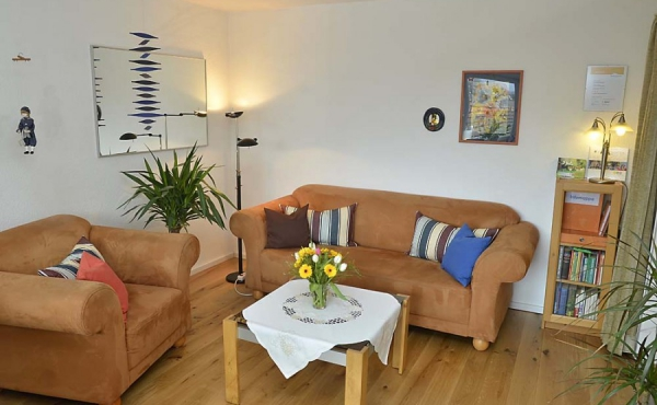 Liebevoll eingerichtetes Wohnzimmer mit Zugang zum Balkon - Ferienwohnung Haus unter der Burg, Gimmeldingen (Pfalz)